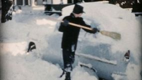 A teenage boy enjoys cleaning off the family car and shovelling snow in Cleveland, Ohio in 1956.