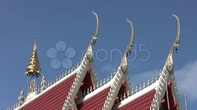 A cool shot of a Buddhist temple roof top complete with ornate decorations.