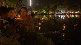 BANGKOK, THAILAND - NOVEMBER 17, 2013: A mother and her sons praying together, before releasing a krathong into a pond in Bangkok, Thailand.