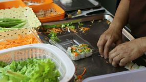 Close up of a Thai food vendor preparing fresh spring rolls at her stall on the streets of Bangkok, Thailand.