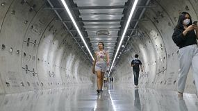 A cute Asian young adult walks through a new underground subway tunnel on the way to her next train stop in Bangkok, Thailand!