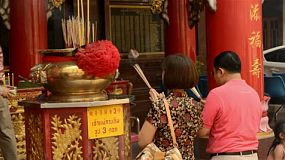 BANGKOK, THAILAND  - FEBRUARY 9, 2013: Thai people making merit and praying for a prosperous new year on the eve of Chinese New Year in Chinatown, Bangkok, Thailand. They are praying at a shrine to Kwan Yin (Kuan Im).