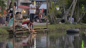 BANGKOK, THAILAND - NOVEMBER 17, 2013: A mother and son, and a young Thai couple release Krathongs into a pond during the Loi Krathong Festival in Bangkok, Thailand.