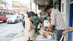 A street vendor sells home made donuts to people on the sidewalk in Bangkok, Thailand.