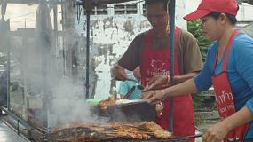 Thai food vendors on a street in Bangkok, selling Som Tum and grilled chicken, pork and fish, with smoke bellowing up from the grill.