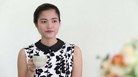 An attractive Asian young adult woman enjoys drinking coffee and spending time in a cafe in Bangkok, Thailand.