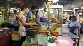 A Thai woman making som tam (papaya salad) at a Bangkok night market. Dolly / tracking shot.