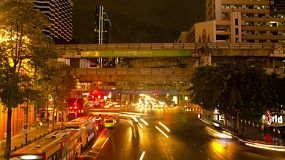 BANGKOK, THAILAND - NOVEMBER 8, 2013: Time lapse of busy traffic at night Ratchaprasong intersection, off Ratchadamri Road, next to Central World, in Bangkok, Thailand. Two skytrain lines. run over the intersection, with Bangkok promotional banners clearly visible on the sky train lines. 4k & 1080p.