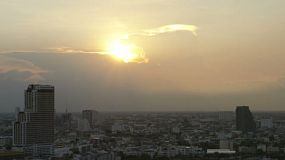 View across the city in Bangkok, Thailand as the sun is setting behind building storm clouds. 1080p timelapse.