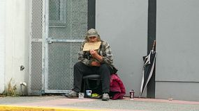 VANCOUVER, BC, OCTOBER 2015: An old homeless man living on the streets waits for someone to come and give him a donation on the streets of Vancouver, BC.