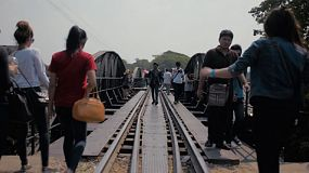 Many Thai and Asian tourists walking along the railroad tracks on the Bridge over the River Kwai in Kanchanaburi, Thailand.