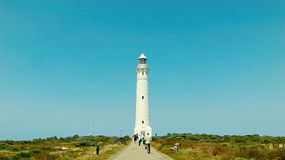Tourists walking down the path to the Cape Leeuwin Lighthouse, on a clear day.