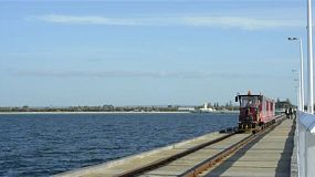 Train travelling down the busselton jetty in south west western australia, full with a load of tourists and with the beautiful shore in the background.