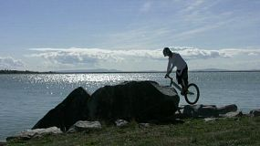 An young man doing trials mountain biking jumping on rocks by the seaside.