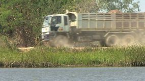 A large delivery truck makes its way down a dirt road beside a pond in rural Thailand.