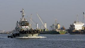 A tugboat passing moored cargo ships moored in the Chao Phraya River in the Bangkok Port, Thailand.
