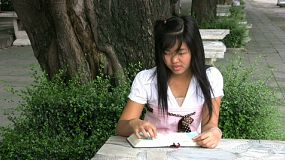 Two attractive female Asian university students sitting on a park bench doing schoolwork together.