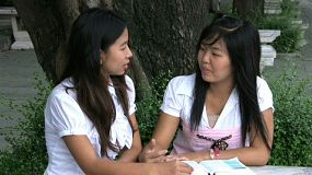 Two Asian Christian girls talking at a table and praying for one another.