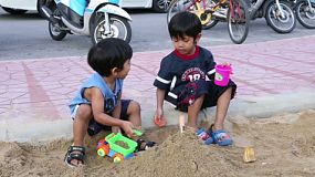 Two cute Asian boys play in a sand box at the park in Bangkok, Thailand.