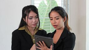 Two attractive female Asian office workers using a tablet to discuss a work project in Bangkok, Thailand.