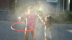 Two cute little Asian sisters enjoy spending time together spraying each other with the garden hose on a gorgeous sunny summer day.