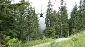 Two people enjoy a fast zip line experience down to the bottom of the mountain through the fog.