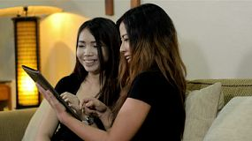 Two young asian women comfortable sitting on a sofa in their loungeroom, playing on a new tablet computer, enjoying themselves smiling and laughing.