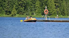 Two friends enjoy spending time together at the lake in their new inflatable row boat on a beautiful summers day.