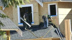 Two men doing roofing work together on a new home in the suburbs.