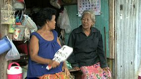 Two old Thai ladies sit on their porch in the slums of Bangkok, Thailand talking and visiting in spite of the heat.