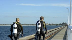 Two scuba divers walking back to shore along the busselton jetty in south west western australia.