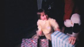 A cute little 2 year old girl diligently hands out Christmas presents to family members on Christmas Day in 1962.