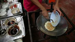 A Bangkok street food vendor mixing eggs in a bowl, and places them in the hot wok cooking an omelette.