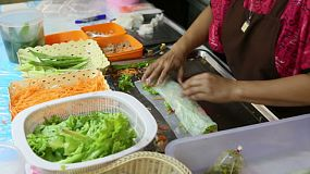 A vendor at a street food stall rolling a fresh spring roll, in Bangkok, Thailand.