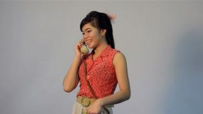 Retro dressed young Asian woman happily talking on the phone - tracking shot.