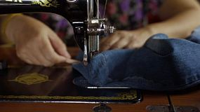Closeup of a woman using a vintage treadle sewing machine to sew a hem on a pair of jeans.