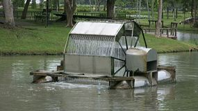 A water aerator does its job spinning around on a lovely pond in Thailand.