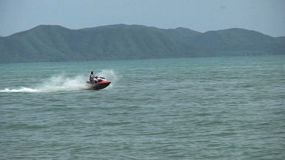 A couple of tourists enjoy racing around on the water in the Gulf of Thailand near Pattaya, Thailand.