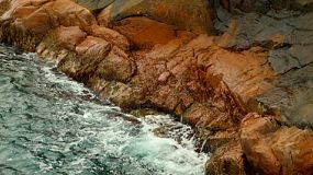 Small waves crashing against rocky coastline at the bast of a cliff in Western Australia.