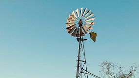 A spinning windmill against blue skies, on a farm in Western Australia.
