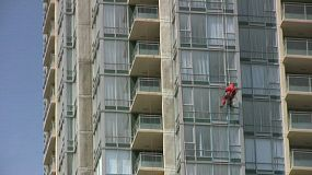 A window washer in a red suit hangs from on high diligently doing his job washing windows on this brand new high rise apartment complex. (HD 1080p30)