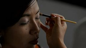 Makeup artist applying eyeshadow to the eyelids of an Asian woman.
