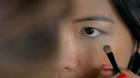 Makeup artist applying eyeshadow for an Asian woman.