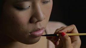 Makeup artist applying lipstick to the lips of an Asian woman.