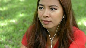 Young asian bobbing her head to music on her headphones, while relaxing in a park.