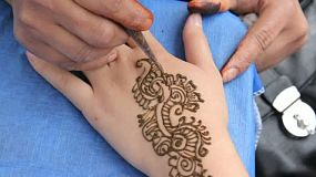 An Indian lady does a henna tattoo on a hand.