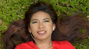 Young asian woman lying on the grass in a park listening to music on her headphones.