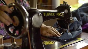 A Thai woman using a vintage sewing machine to sew jeans.