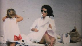 A mom smokes a cigarette and relaxes at the beach in Florida with her family in 1967.