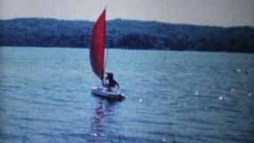 Two women enjoy some time in a sailboat on a lake on a summer's day in 1962.